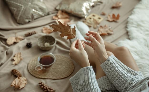 Dziewczyna w sweterku z dzianiny trzyma w dłoni jesienny liść