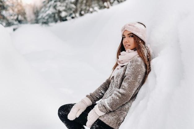 Dziewczyna w swetrze i rękawiczkach zimą stoi na tle pokrytym śniegiem.