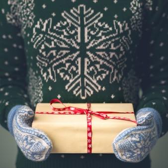 Dziewczyna w swetrze noworocznym trzyma prezent. prezenty dla mężczyzn. wesołych świąt. prezent dla dziewczynki. sweter z ozdobą świąteczną. dzianinowa sukienka.