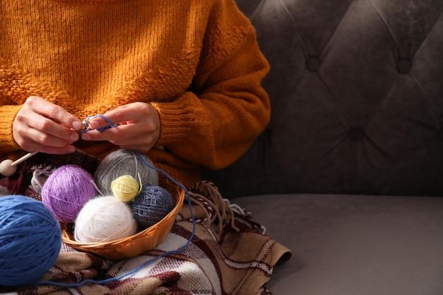 Dziewczyna w swetrze robi na drutach, siedząc na kanapie, miejsce na tekst