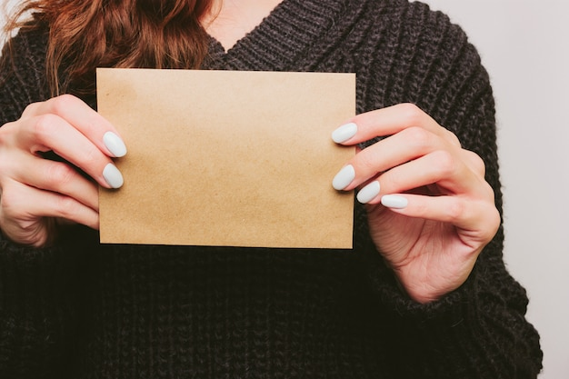 Dziewczyna w swetrze trzyma pustą kartę z papieru rzemieślniczego formatu a5. prezentacja. biały manicure