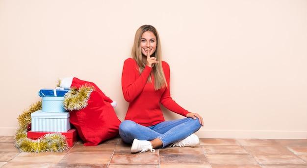 Dziewczyna w święta bożego narodzenia, siedząc na podłodze, robi gest ciszy