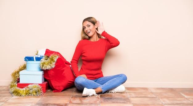 Dziewczyna w święta bożego narodzenia, siedząc na podłodze, słuchając czegoś