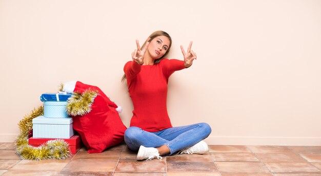 Dziewczyna w święta bożego narodzenia, siedząc na podłodze, uśmiechając się i pokazując znak zwycięstwa