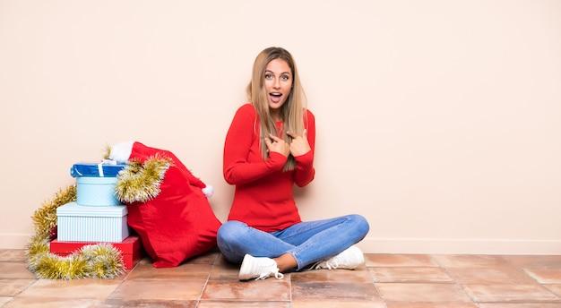 Dziewczyna w święta bożego narodzenia, siedząc na podłodze z okazji zwycięstwa