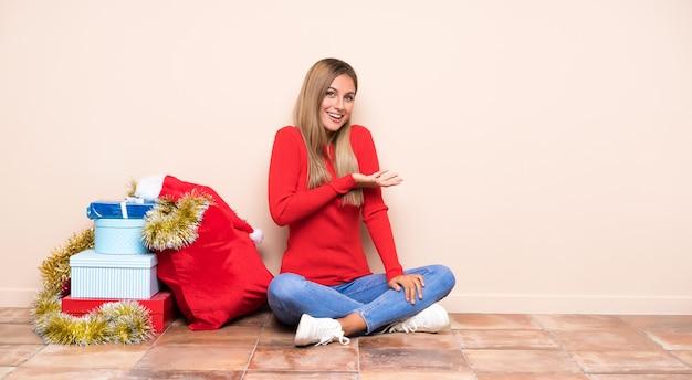 Dziewczyna w święta bożego narodzenia siedzi na podłodze, rozkładając ręce na bok, zapraszając do siebie