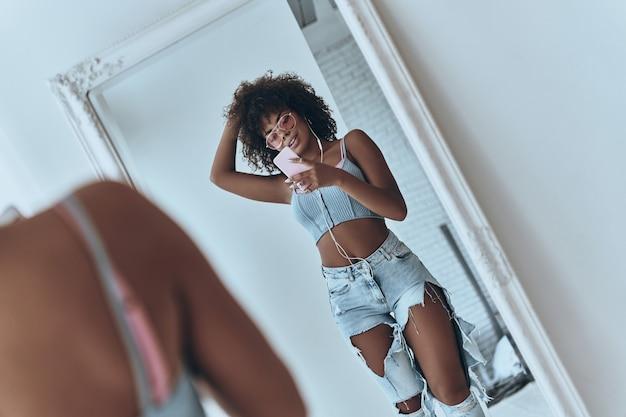 Dziewczyna w świetnym stylu. odbicie pięknej młodej afrykańskiej kobiety słuchającej muzyki i trzymającej rękę we włosach podczas robienia selfie w lustrze w domu