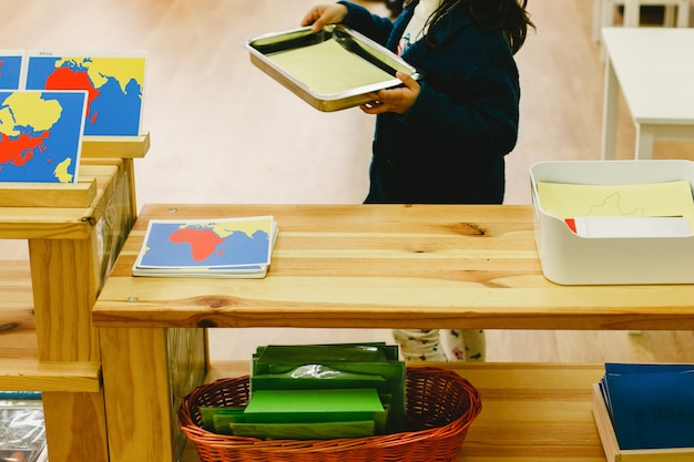 Dziewczyna w swojej szkole montessori przenosi tace z materią