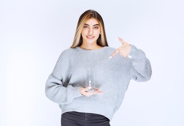 Dziewczyna w szarej bluzie trzyma szklankę czystej wody.