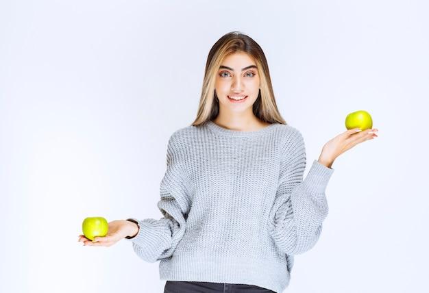 Dziewczyna w szarej bluzie, trzymając w ręku zielone jabłko.