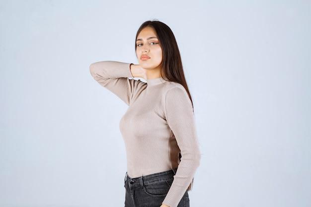 Dziewczyna w szarej koszuli daje pozytywne i atrakcyjne pozy.