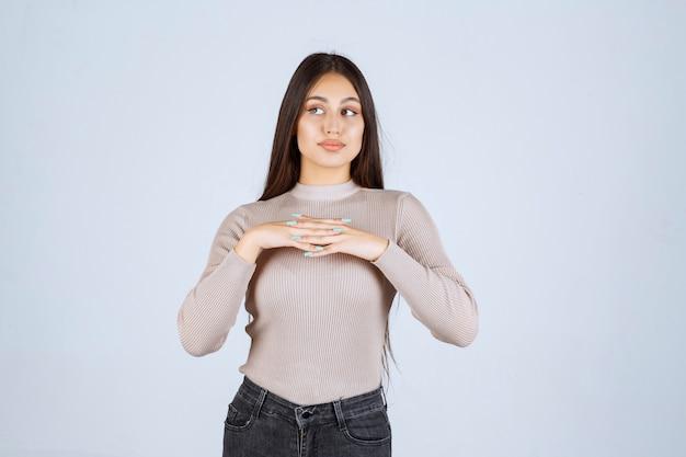 Dziewczyna w szarej koszuli daje zachęcające i uwodzicielskie pozy.