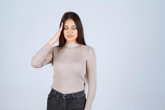 Dziewczyna w szarej koszuli ma ból głowy lub zmęczenie.