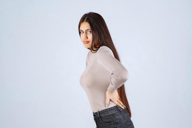Dziewczyna w szarej koszuli ma bóle pleców.