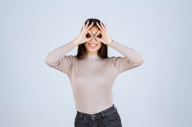 Dziewczyna w szarej koszuli patrząc przez palce.