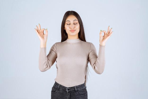 Dziewczyna w szarej koszuli podejmowania medytacji.
