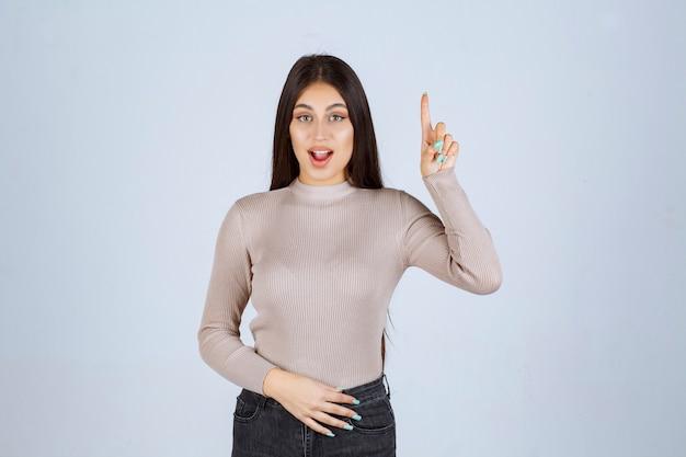 Dziewczyna w szarej koszuli pokazująca coś powyżej i podekscytowana.