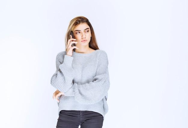 Dziewczyna w szarej koszuli rozmawia przez telefon.