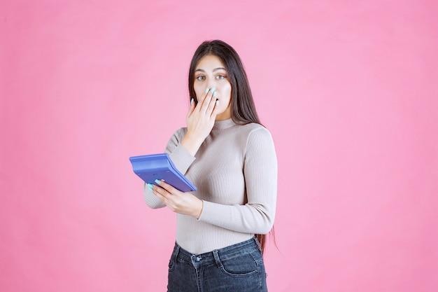 Dziewczyna w szarej koszuli trzyma niebieski kalkulator i pokazuje znak ciszy, gdy pracuje