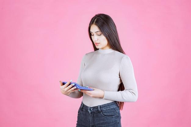 Dziewczyna w szarej koszuli trzyma niebieski kalkulator, ogląda go i pracuje z nim