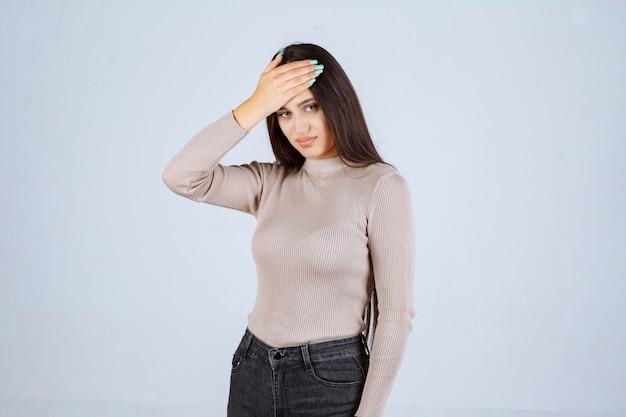 Dziewczyna w szarej koszuli, trzymając głowę z powodu bólu głowy.