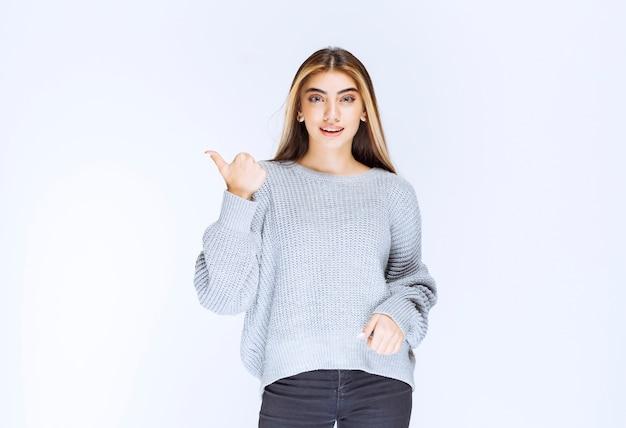 Dziewczyna w szarej koszuli, wskazując gdzieś lub na kogoś.