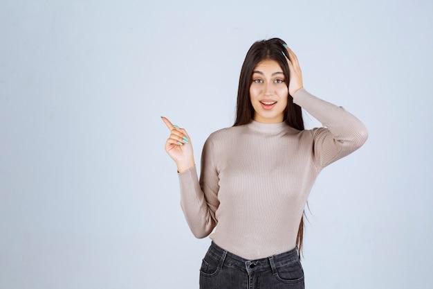 Dziewczyna w szarej koszuli, wskazując na coś po lewej stronie.