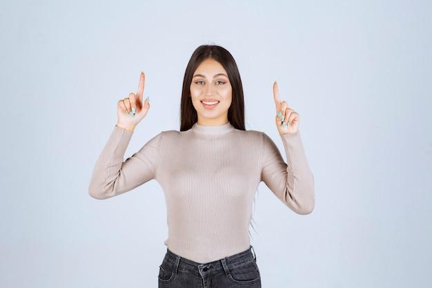 Dziewczyna w szarej koszuli, wskazując na coś.