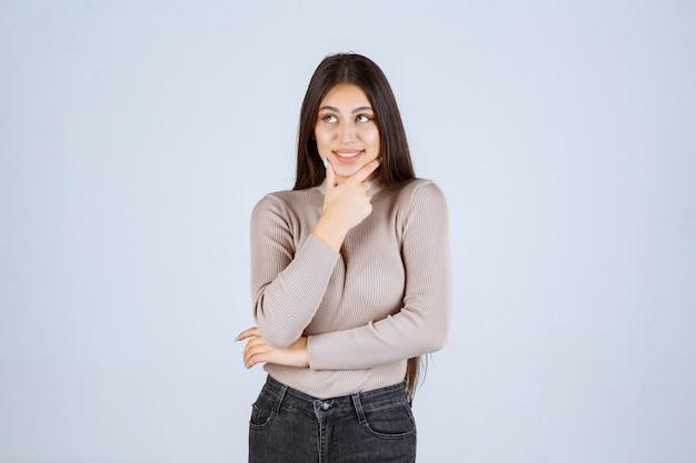 Dziewczyna w szarej koszuli wygląda na podekscytowaną i zaskoczoną.