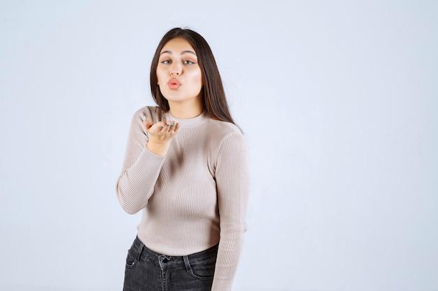 Dziewczyna w szarej koszuli wysyłając miłość swoim fanom.