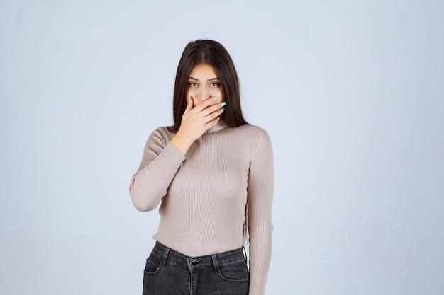 Dziewczyna w szarej koszuli zakrywającej jej twarz.