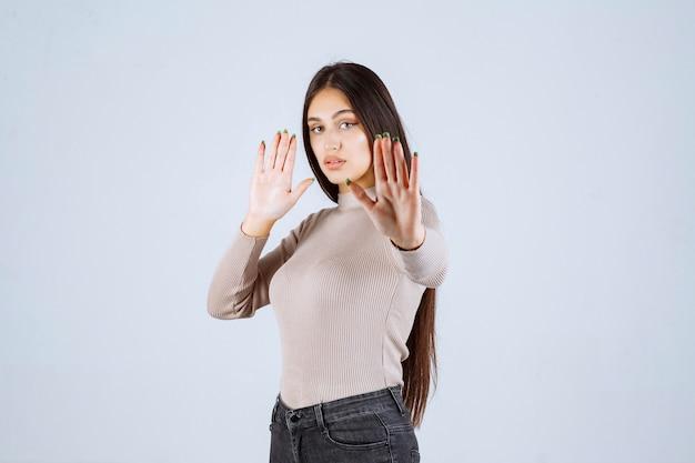 Dziewczyna w szarej koszuli zatrzymuje się i zapobiega czemuś.