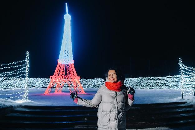 Dziewczyna w szarej kurtce zimą z wieczornymi światłami palącymi się na świątecznej ulicy