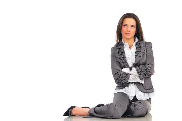 Dziewczyna w szarym garniturze i czarnych butach siedzi na podłodze z rękami skrzyżowanymi i patrzy w bok. na białym tle na białej ścianie