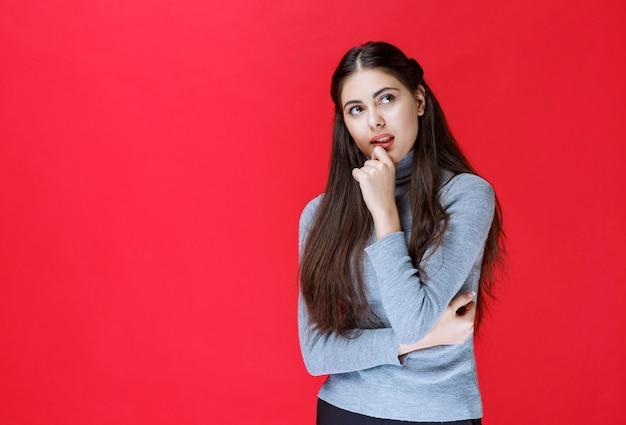 Dziewczyna w szarym swetrze mocno myśli i próbuje zapamiętać.