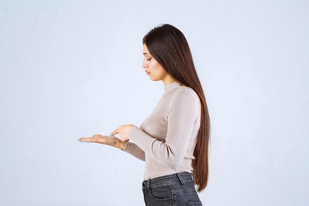 Dziewczyna w szarym swetrze, patrząc na coś na jej rękę.