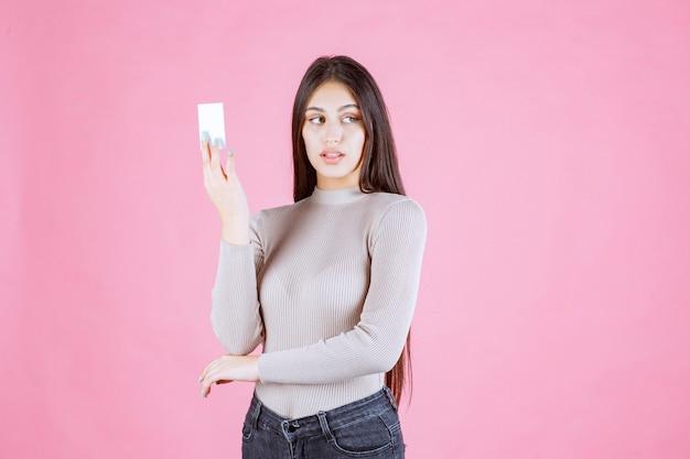 Dziewczyna w szarym swetrze pokazuje i prezentuje swoją wizytówkę