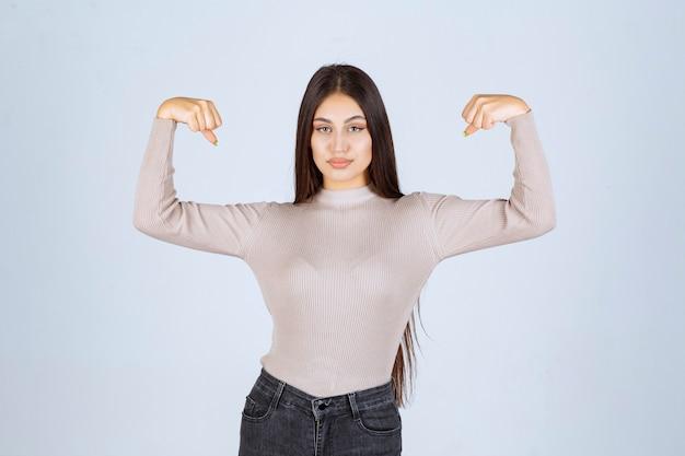 Dziewczyna w szarym swetrze pokazuje jej pięści i siłę.