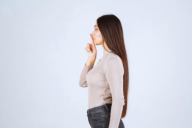 Dziewczyna w szarym swetrze robi cichy znak.