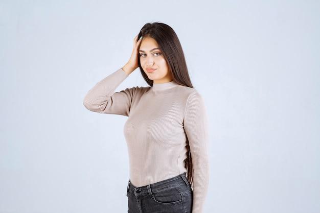Dziewczyna w szarym swetrze, trzymając jej twarz i głowę.