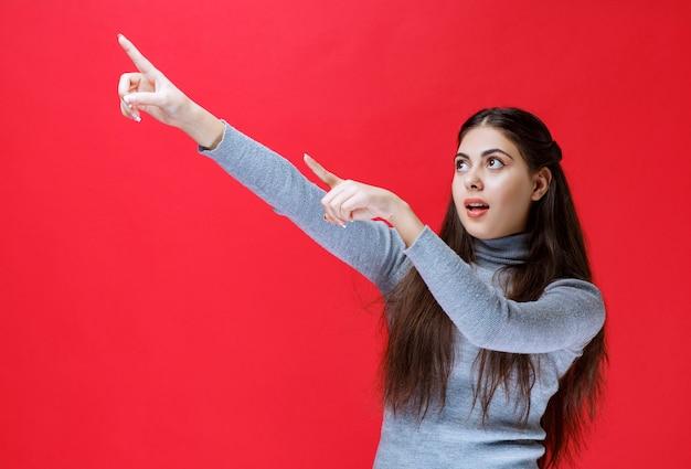 Dziewczyna w szarym swetrze, wskazując na coś za.