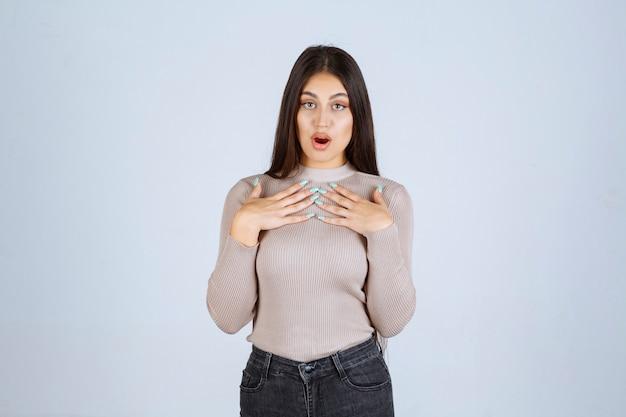Dziewczyna w szarym swetrze, wskazując na siebie.
