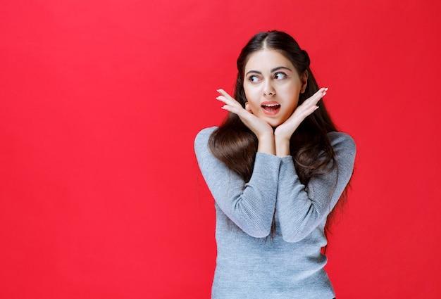 Dziewczyna w szarym swetrze wygląda na wyjątkowo przerażoną i zdezorientowaną.