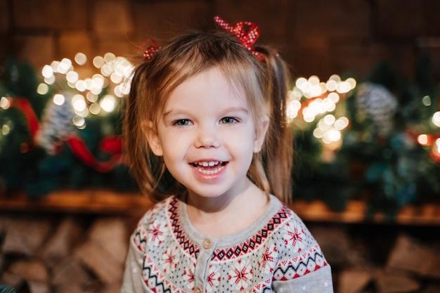 Dziewczyna w szarym swetrze z kucykami na tle noworocznej girlandy