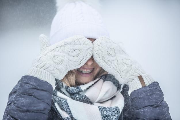 Dziewczyna w szelkach i zimowych ubraniach zasłania oczy wełnianymi rękawiczkami.