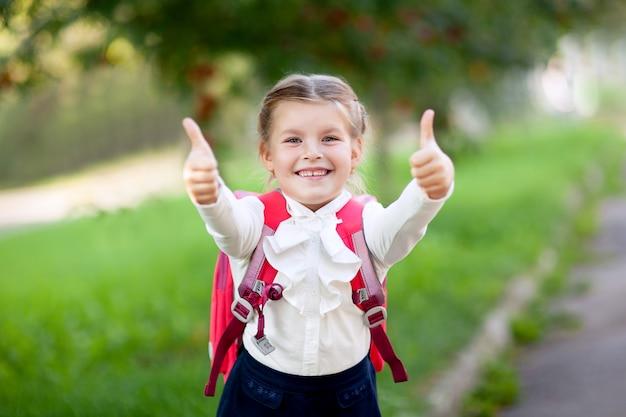 Dziewczyna w szkole podstawowej ze szkolnym plecakiem na zewnątrz