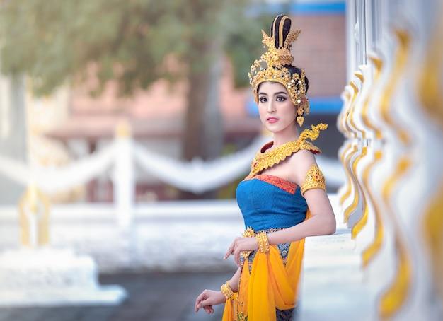 Dziewczyna w tajskiej sukience narodowej. uśmiechała się, witając i robiąca dłoń. sawasdee to pozdrowienie z tajlandii.