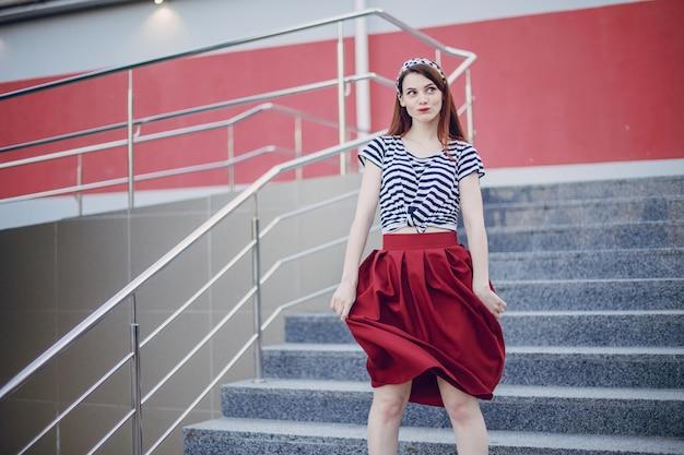 Dziewczyna w trybuny trzymając czerwoną spódnicę