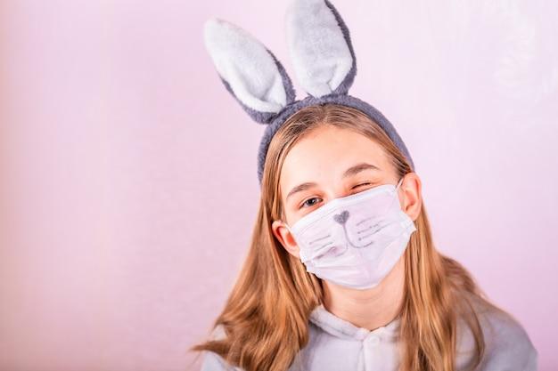 Dziewczyna w uszach królika królika na głowie i masce ochronnej z kolorowymi jajkami na różowym tle.