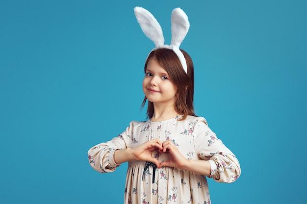 Dziewczyna w uszach królika robi gest serca na białym tle nad niebieską ścianą